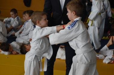 Dwóch chłopców pojedynkuje się. Trzymają się za ramiona. Za nimi stoi sędzia. W tle dzieci leżą na macie.