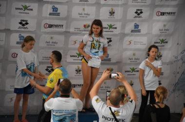 Trzy dziewczynki stoją na podium. Odbierają nagrody za zawody pływackie.
