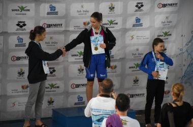 Trzy dziewczynki stoją na podium. Odbierają nagrody za zawody pływackie. Dwie dziewczynki podają sobie ręce.