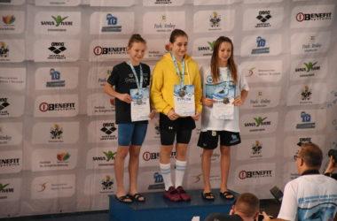 Trzy dziewczynki stoją na podium. Uśmiechają się i odbierają nagrody za zawody pływackie.