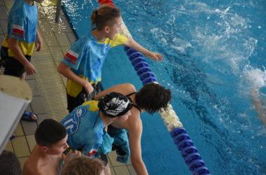 Młodzi zawodnicy dopingują swoich kolegów na brzegu basenu.