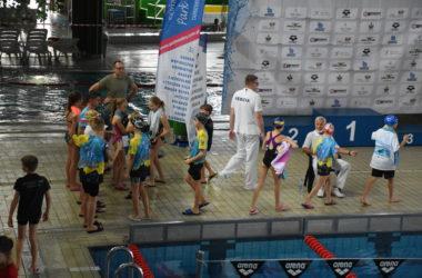 Młodzi zawodnicy stoją w grupie przy basenie.