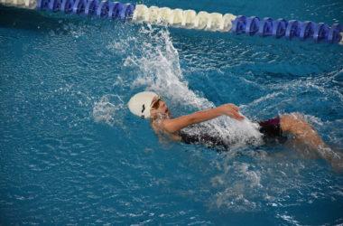 Zawodnik płynie w basenie na wynaczonym torze.