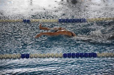 Zawodniczka płynie w basenie po wyznaczonym torze.