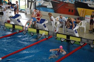 Młodzi zawodnicy skaczą z wyznaczonych im skoczni. Na pierwszym planie dziewczyna pływa w basenie.
