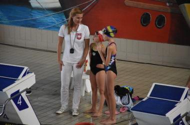 Młode zawodniczki stoją razem z sędzią przy basenie.