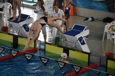 Zawodniczka skacze na główke do basenu z wyznaczonej skoczni.