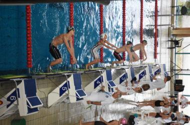 Zawodnicy rozpoczynają wyścig. Odpychają się od murku w basenie.