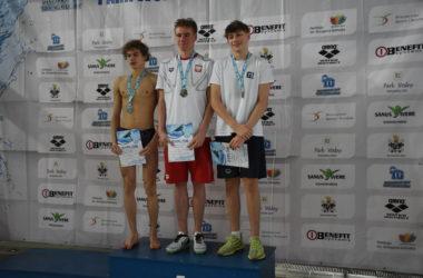 Trzech zawodników stoi na podium. Pozują do zdjęć.