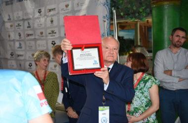 Mężczyzna trzyma pamiątkowy dyplom.