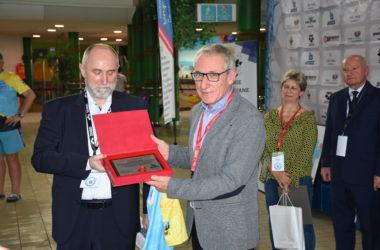 Dwóch mężczyzn pozuje do zdjęcia z dyplomem