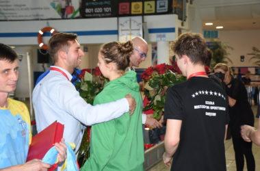 Zawodnicy wręczają kwiaty organizatorom.