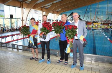 Organizatorzy pozują z kwiatami. W tle basen.