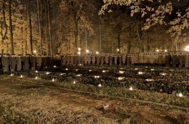 Żołnierze stoją na obrzeżach cmentarza.