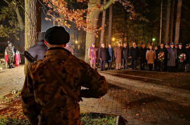 Na pierwszym planie żołnierz stoi tyłem. Na przeciwko niego, na drugim planie stoją przedstawiciele władz ustawieni w rzędzie.