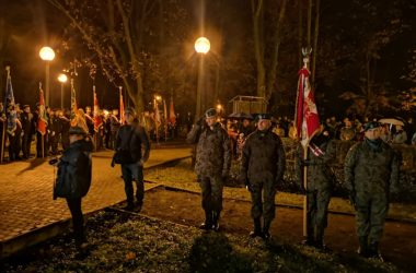 Na pierwszym planie czterech żołnierzy stoi w rzędzie. W tle po lewej stoją przedstawiciele władz z flagami. Po prawej stoją zebrani mieszkańcy.