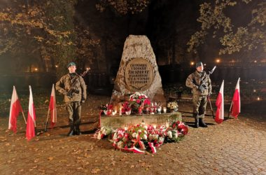 Pomnik żołnierzy poległych w II wojnie światowej. Pod pomnikiem leżą kwiaty i zapalone znicze. Dwóch żołnierzy stoi po obu stronach pomnika. Obok nich są ustawione biało-czerwone flagi.
