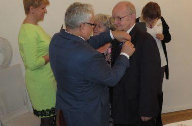 Burmistrz miasta wręcza medale zadowolonym jubilatom.