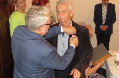 Burmistrz miasta wręcza medale jubilatowi.