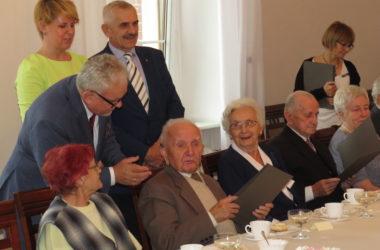Nagrodzeni jubilaci pozują do zdjęcia z Burmistrzem miasta w Sali Ślubów Urzędu Miejskiego.