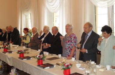 Nagrodzeni jubilaci wznoszą toast w Sali Ślubów Urzędu Miejskiego.