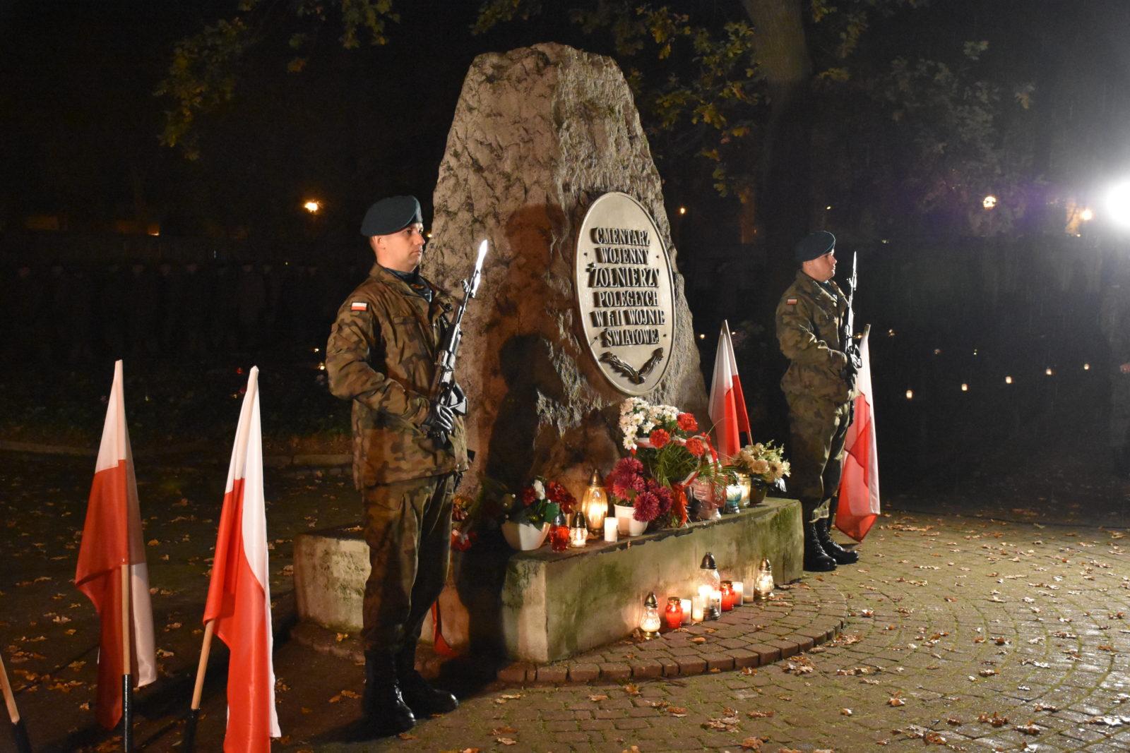 Dwóch żołnierzy stoi pod pomnikiem żołnierzy poległych.