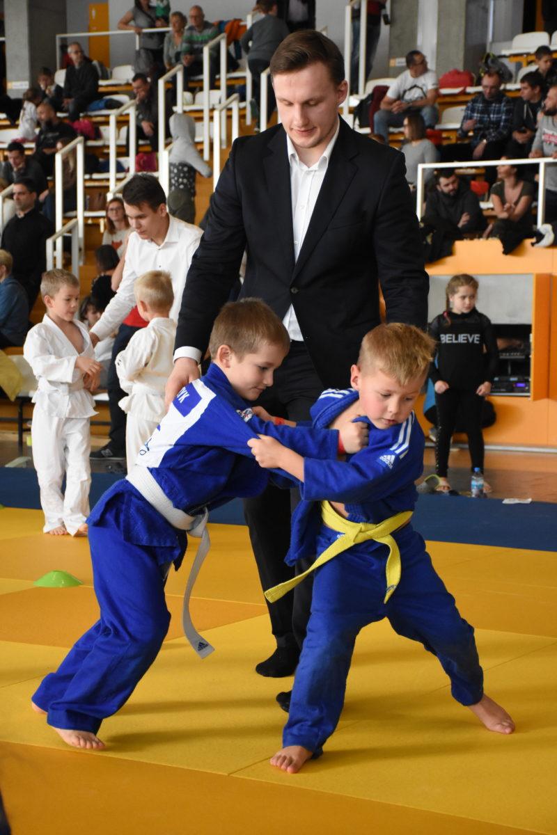 Zawody Judo w Hali Sportowej. Dwóch chłopców walczy z sobą na macie. Przy chłopcach stoi sędzia.
