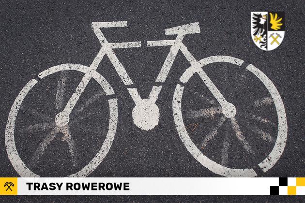 Plakat Tras rowerowych. Przedstawia znak rowera narysowany na drodze.