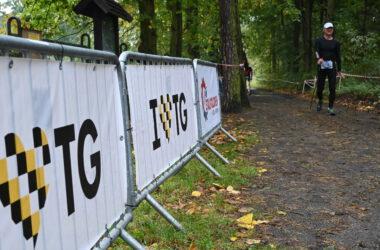 Zawodnicy przed startem i barierki z plakatami