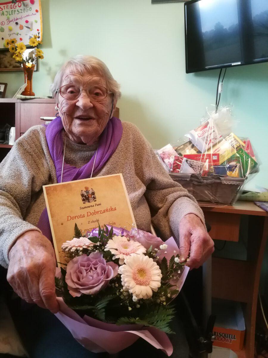 Pani Dorota skończyła 100 lat - zdjęcie jubilatki z dyplomem, kwiatami i koszem słodyczy