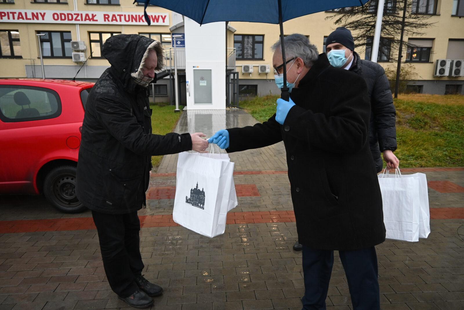 Burmistrz Arkadiusz Czech przekazuje torby z pulsoksymetrami