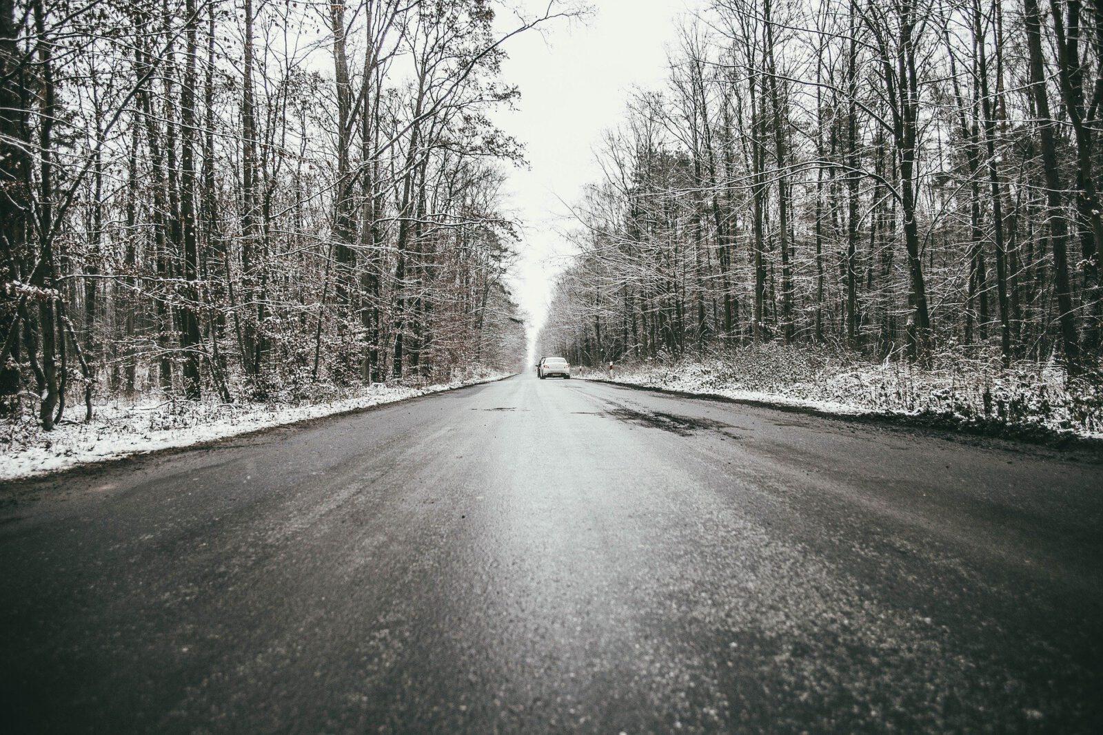 Zimowa droga przez las, pokryta lodem