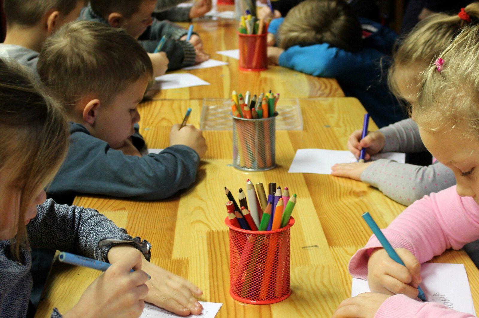 Dzieci w przedszkolu rysują kredkami
