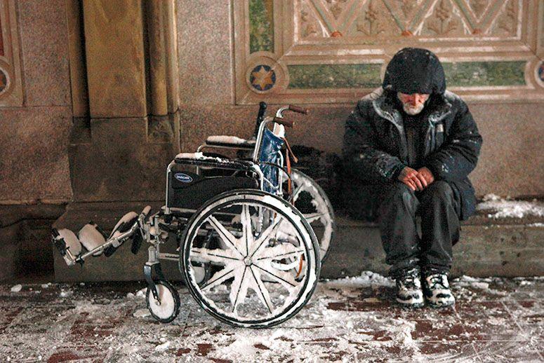 Bezdomny z wózkiem inwalidzkim. Sceneria zimowa.