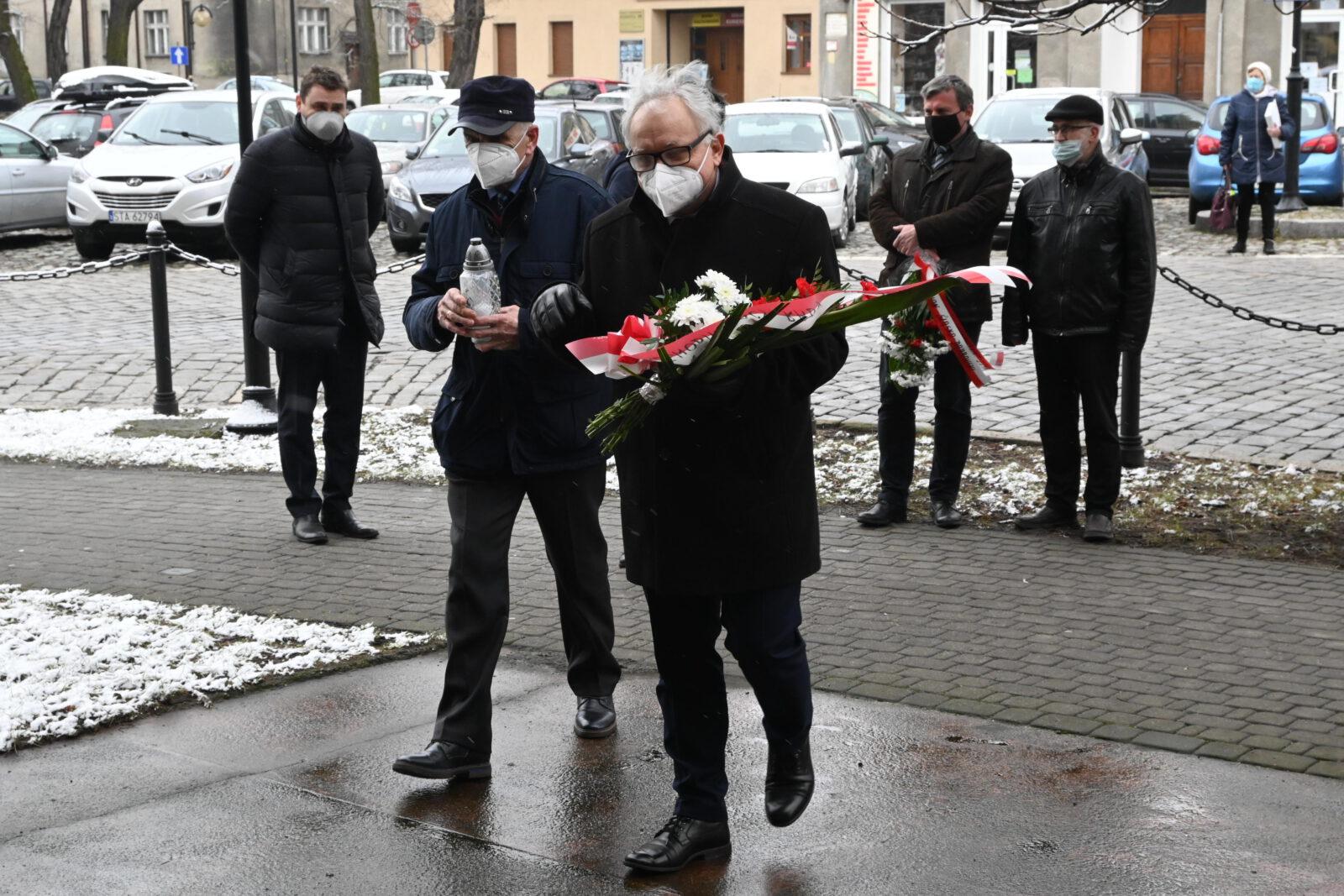 Burmistrz Arkadiusz Czech i wiceprzewodniczący rady miejskiej Franciszek Nowak składają znicze i kwiaty pod pomnikiem katyńskim