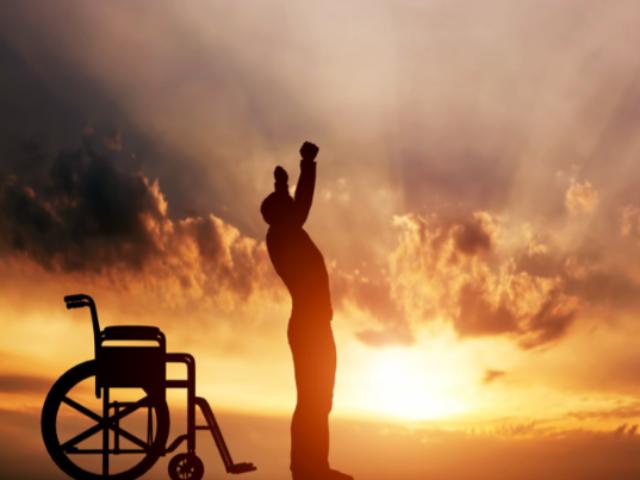 Zarys stojącego mężczyzny z uniesionymi w górę rękami. Za mężczyzną zarys wózka inwalidzkiego. W tle niebo podczas zachodu słońca.