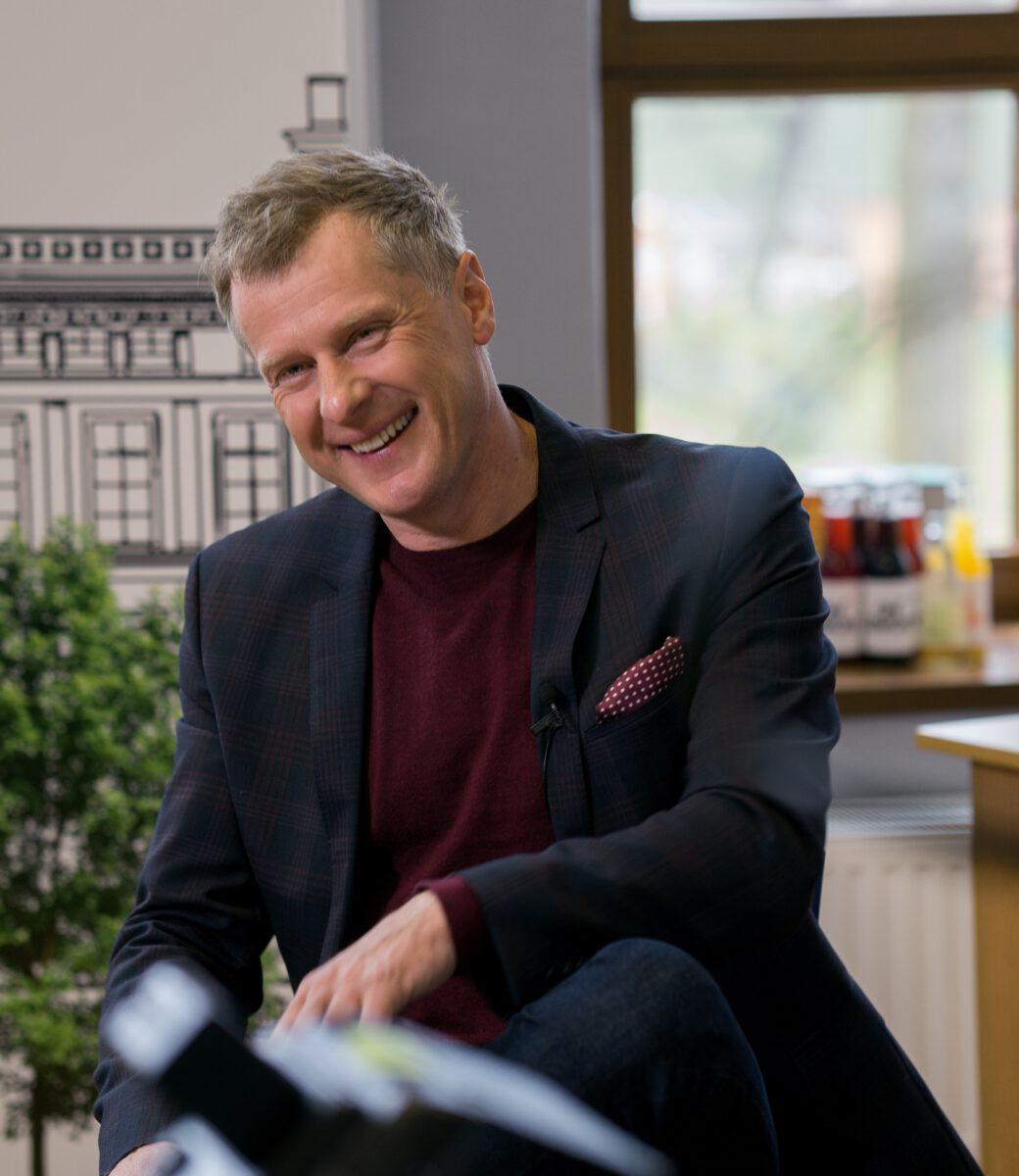Uśmiechnięty Krzysztof Respondek siedzi na krześle w ciemnej marynarce.