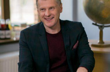 Uśmiechnięty Krzysztof Respondek siedzi na krześle w ciemnej marynarce. W tle okno i globus.