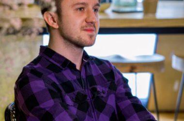 Uczestnik reportażu w koszuli w fioletowo czarną kratę.