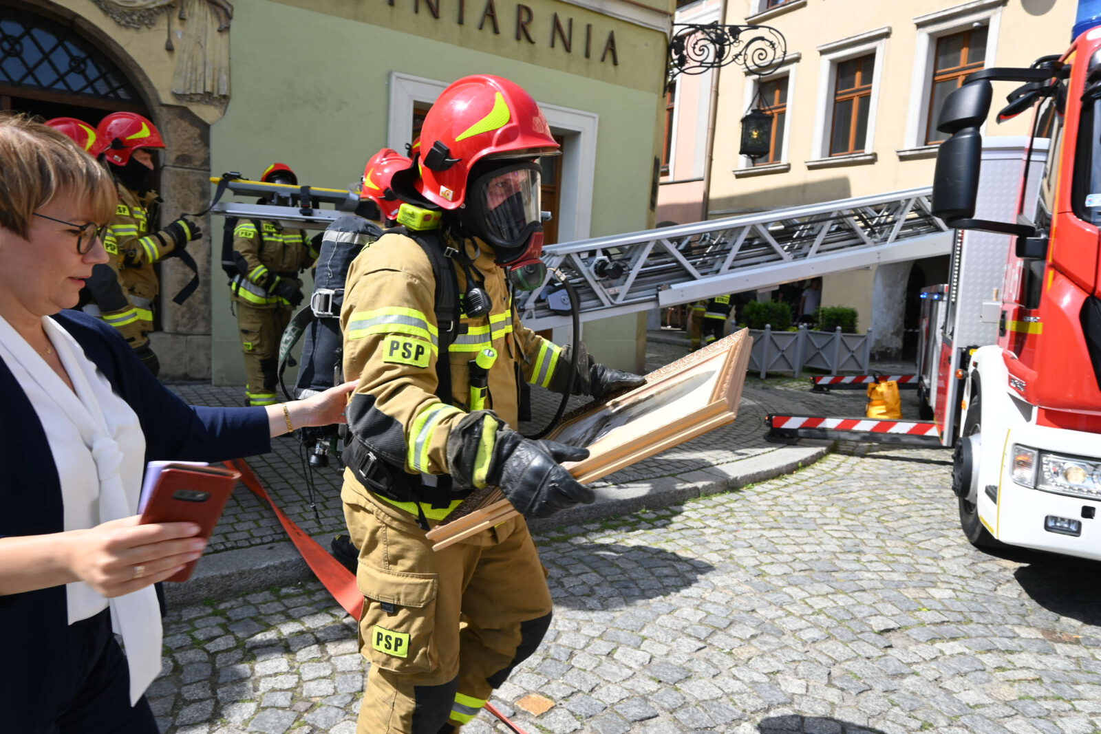 Dyrektor Muzeum Beata Kiszel ze strażakiem w masce w wynoszącym zbiory z Muzeum