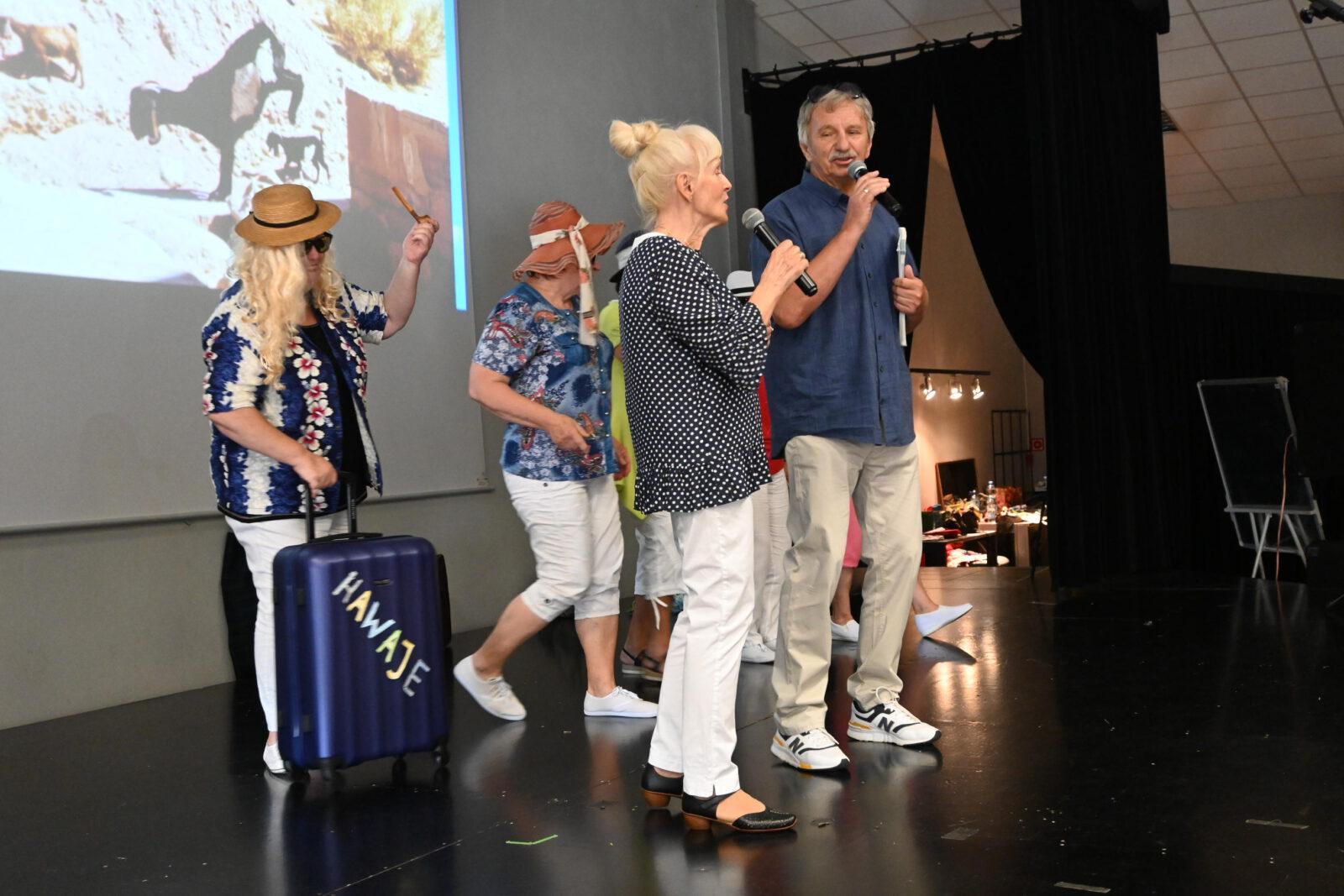 Na scenie w pierwszym rzędzie kobieta i mężczyzna z mikrofonem a z tyłu kobiety w kapeluszach i jedna z walizką w dłoni