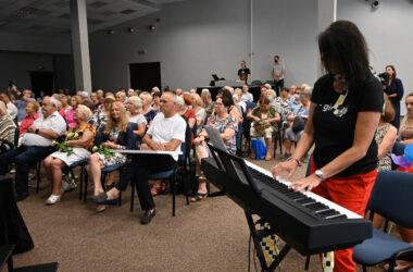 Pani grająca na keyboardzie wśród publiczności
