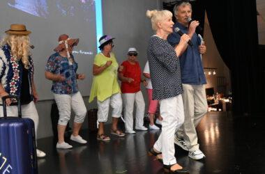 Na scenie w pierwszym rzędzie kobieta i mężczyzna z mikrofonem a z tyłu pięć kobiet w kapeluszach