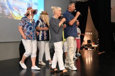 Na scenie w pierwszym rzędzie kobieta i mężczyzna z mikrofonem a z tyłu dwie kobiety w kapeluszach