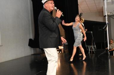 Na scenie śpiewający mężczyzna z mikrofonem i tańcząca pani z piórkiem we włosach