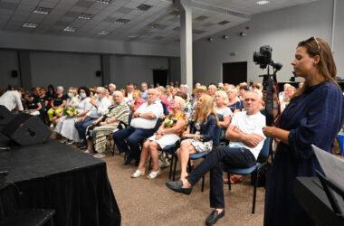 Z lewej strony publiczność a z prawej kobieta z aparatem w dłoniach
