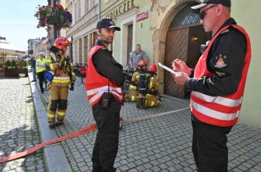 Pięciu strażaków w mundurach przed Muzeum
