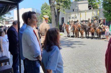 Publiczność a w tle ułani na koniach.