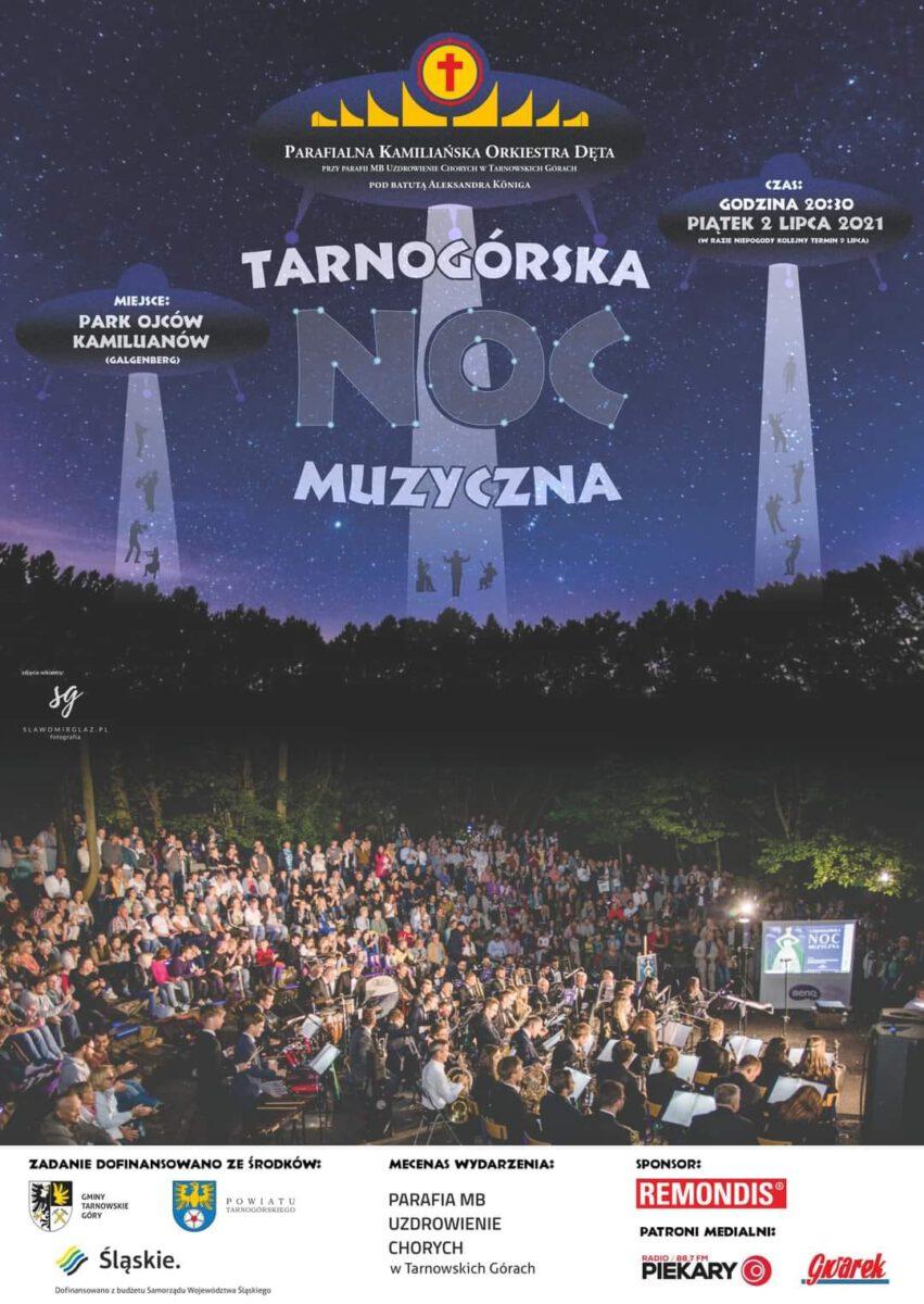 Plakat z trzema latającymi obiektami na rozgwieżdżonym niebie. W dole orkiestra z publicznością na tle drzew.