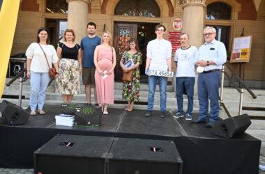 Siedmioro laureatów loterii przed tarnogórskim Ratuszem z Burmistrza Arkadiuszem Czechem